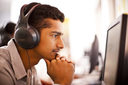 Man with headphones reading from a computer screen.