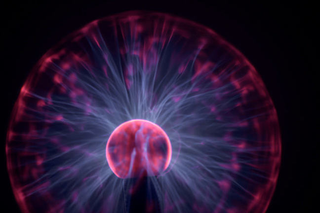 Plasma globe emitting red rays to indicate global scale.