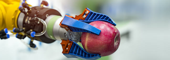 Robotic arm holding an apple in a science lab