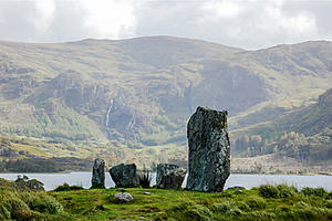 Standing stones on a grass mound set against a backdrop of mountains and a lake.