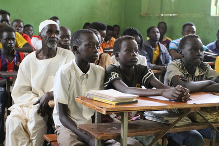 Young teenage boys and a man sitting at desks in a classroom