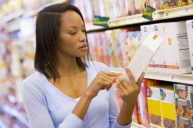 Female shopper checking food label in a supermarket