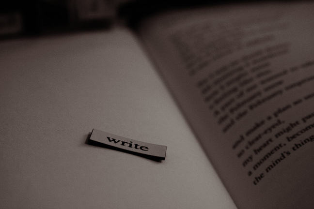 An open book with the word 'write' on a separate page.