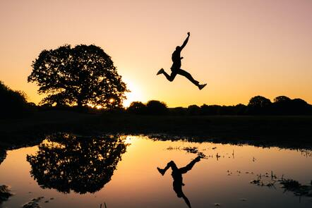 Silhouette of a person jumping over a body of water at dusk