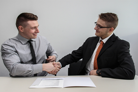 Two suited men st at a table, shaking hands in agreement.