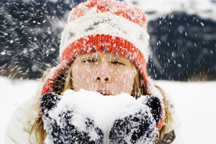 Woman blowing snow outside