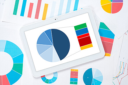 A tablet showing a pie chart, on top of pieces of paper showing lots of different types of charts.