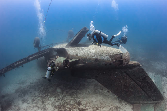 SCUBA divers exploring the upturned fuselage of an underwater aircraft wreck