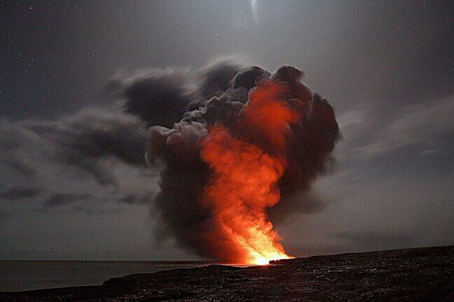A volcano spouts hot ash into a darkened sky