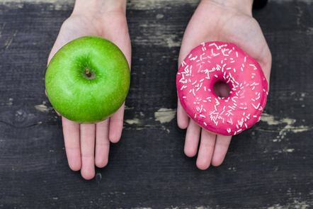 2 hands - 1 holding an apple and the other one holding a donut