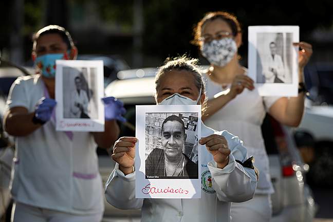Three healthcare workers, in their uniforms and face masks, each hold up a photo of one of their colleagues who has passed away from the virus.