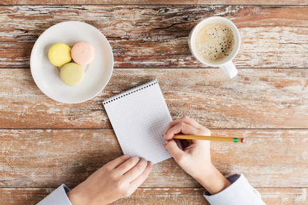 Close up of female hands with with notebook, pencil, coffee and cookies on table