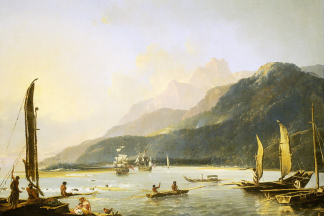 A view of Maitavie Bay, with canoes and people in foreground and sailing ships behind. There is blue sky and mountainous landscape and sunshine on calm water.