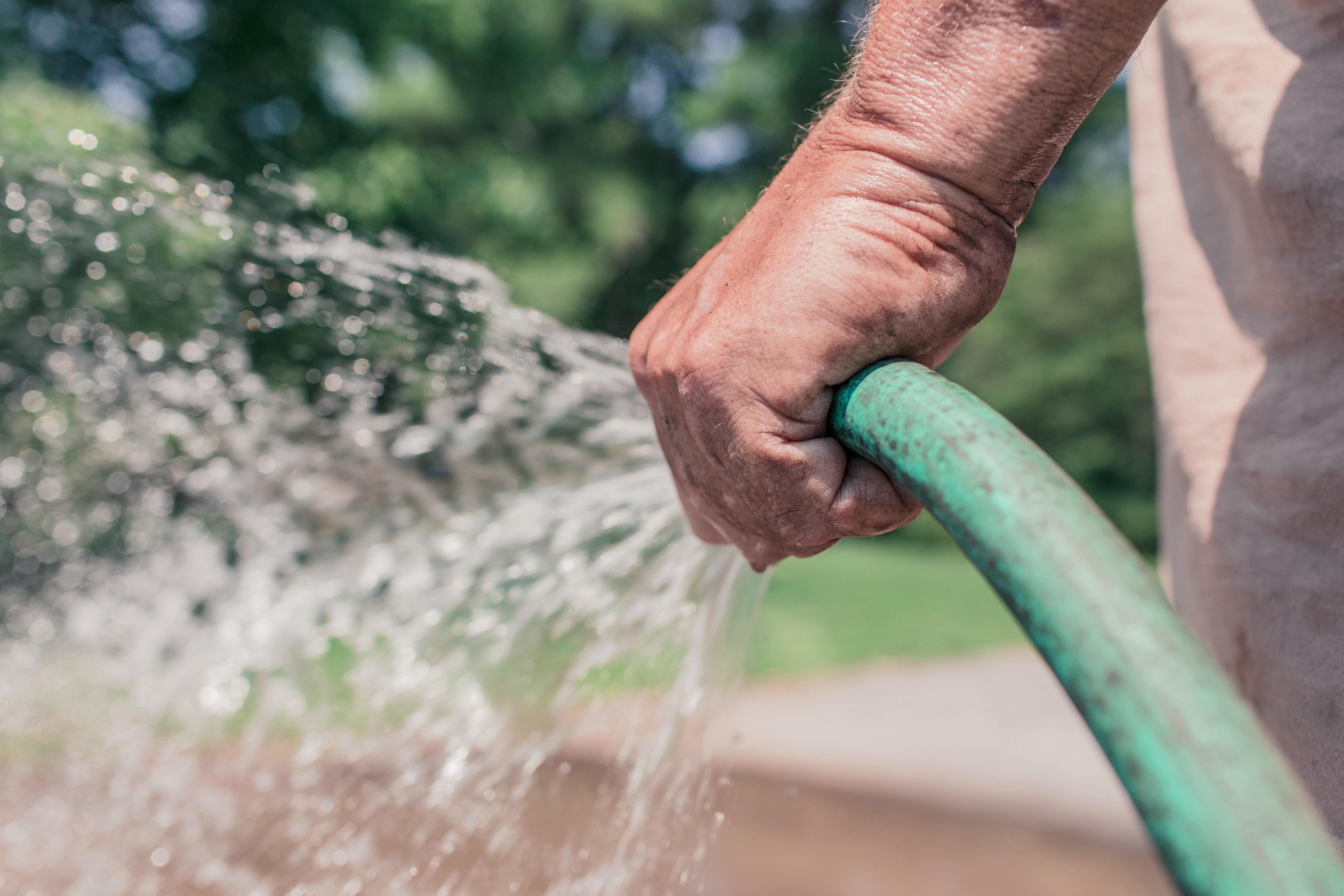 a male hand holding a hose
