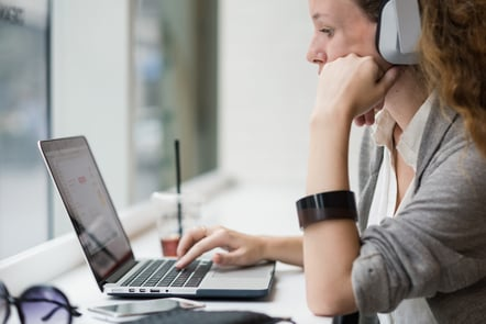 Woman at a desk using a laptop with headphones on