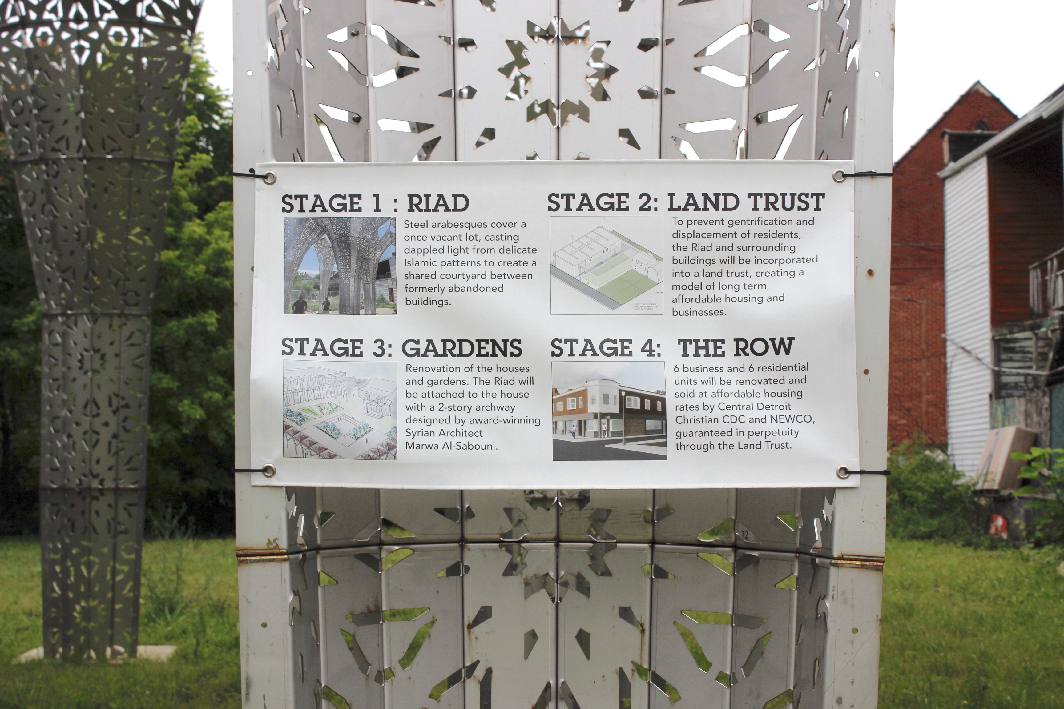 Photograph of metal structure in the foreground of a yard, with a sign attached listing four stages of the American Riad project.
