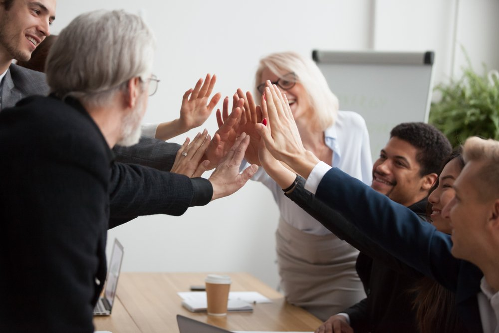 Group of diverse workers high five around a meeting table