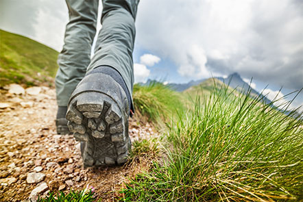 Close up of the shoes of someone hiking on a mountain trail.