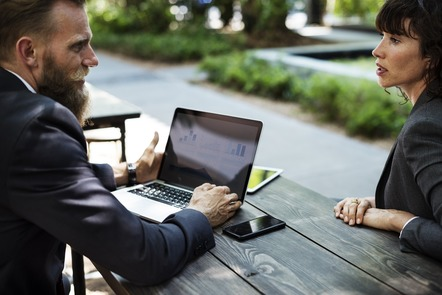 two people talking around a laptop at a picnic table
