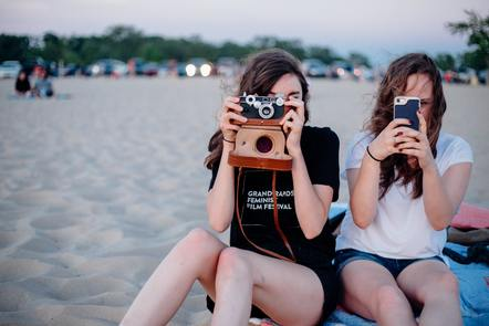 Two women, on with a smart phone, one with a traditional camera. Kendra Kemp, Unsplash