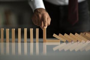 Image of finger knocking down dominoes