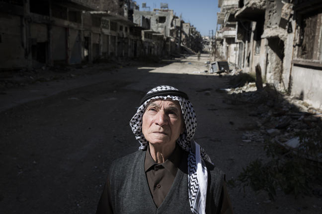 Image of elderly man amidst rubble in Homs