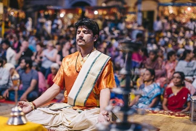 man meditating on stage before an audience