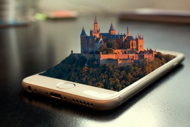 A large fortified building (perhaps a palace or monastery) emerges from the screen of a mobile phone.