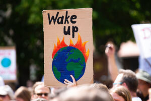 Climate change protester holds up a sign depicting the world on fire within a group of protesters