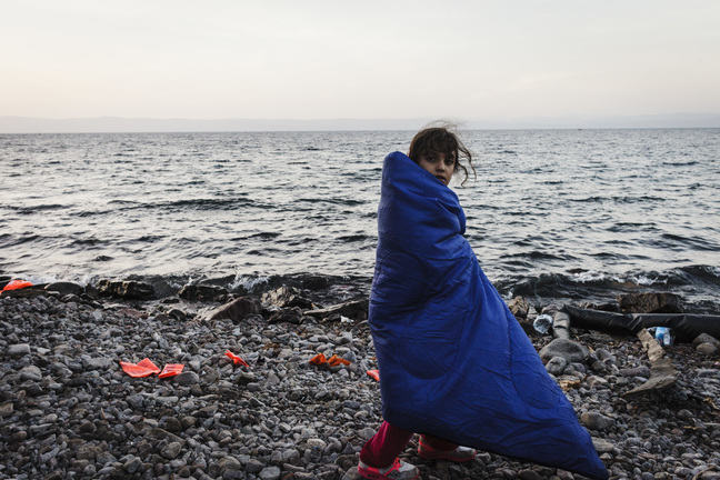 Image of girl wrapped in blanket by the sea