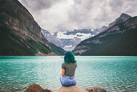Woman on lake shore surrounded by mountains