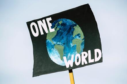 """A hand painted sign that reads """"One World"""" in white font against a black piece of cardboard with the blue and green planet painted over."""