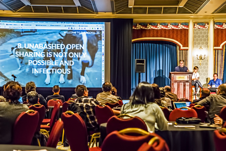 A photo taken at a conference. People sit around tables facing a speaker at a lectern and a large screen. The screen is displaying a slide with a photograph of a dog and the words '8. Unabashed open sharing is not only possible and infectious.