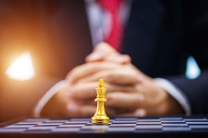 Businessman hand with businessman goal with chess.