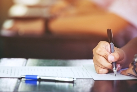 A person using a pen fills in a written form.