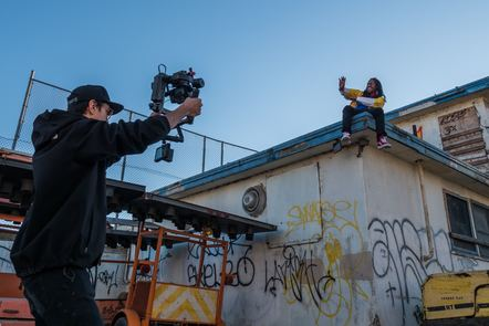 Man taking video of person on a roof