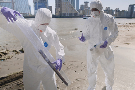 Two forensic scientists at the crime scene on the beach. The scientist on the right is instructing the other, as they store evidence from the crime scene.