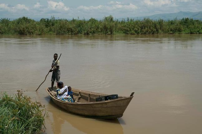A woman holding her small child in her arms sits in a small wooden boat as it is steered across a river my a male holding a paddle.