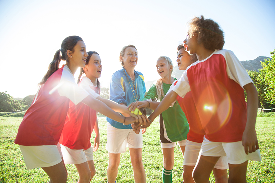 Girls' soccer team (aged 12-13) doing a high five while preparing for a match