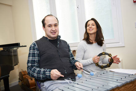 A man is smiling and playing the xylophone with sticks next to a woman playing the tambourine