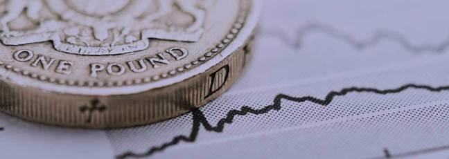 A coin sits on top of a line graph on a piece of paper – a metaphor for financial planning.