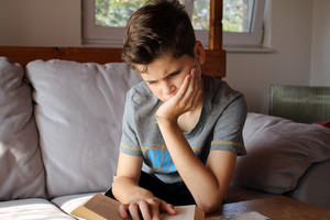 A dyslexic student struggles to read a book