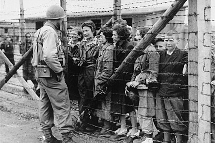 Women and children survivors in Mauthausen speak to an American liberator through a barbed wire fence.