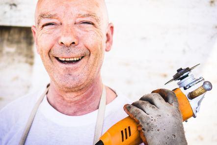 Smiling worker holding orange angle grinder