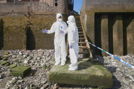 Two forensic scientists arrive at a crime scene, both are wearing protective clothes covering their full bodies.
