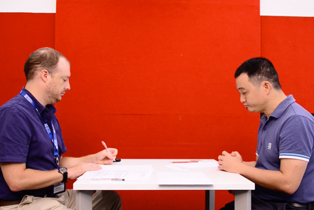 An IELTS interview with examiner on the left and candidate on the right