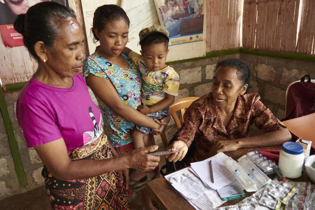 A female health care practitioner hands over medication to a female patient standing nearby as another woman holding her small child looks on.