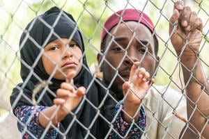 Muslim mid adult black man holding his daughter looking through a fence