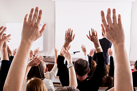 A classroom full of raised hands wanting to answer a question given by the teacher at the front of the room.