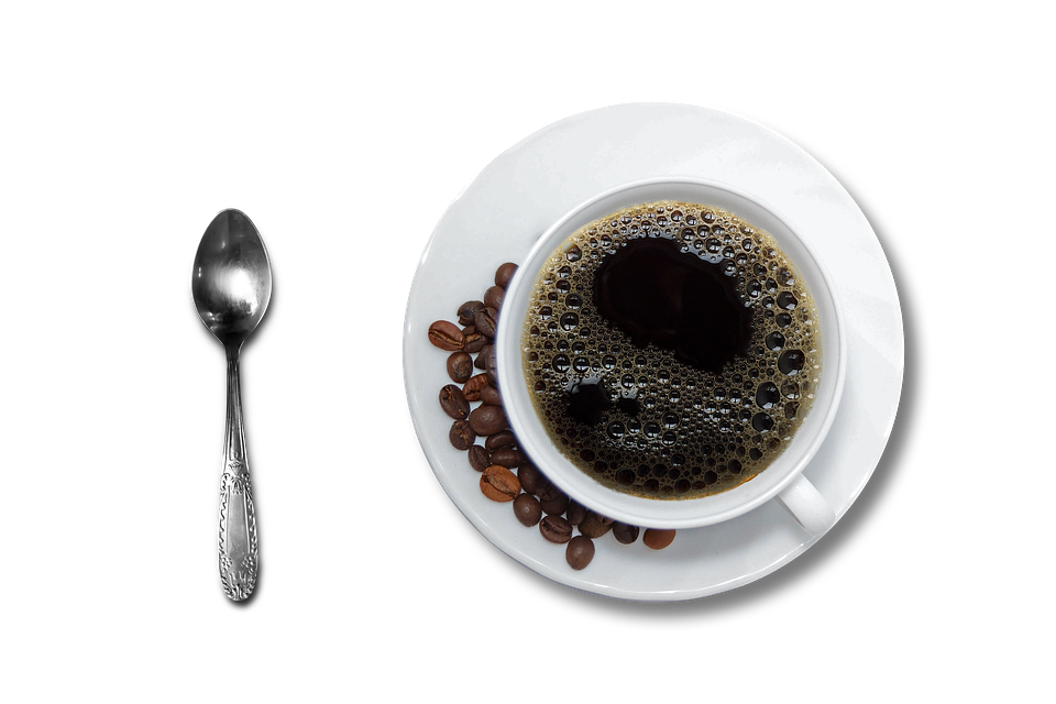 A cup of coffee together with some roasted coffee beans and a teaspoon.